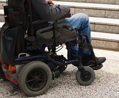 Personne en chaise roulante devant un escalier